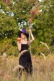 Blondes Mädchen im Hexenkostüm mit Besenstiel Stockfoto