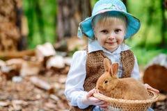 Blondes Mädchen im Hut, der ein Kaninchen hält Lizenzfreie Stockbilder