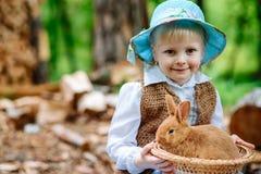 Blondes Mädchen im Hut, der ein Kaninchen hält Lizenzfreie Stockfotos
