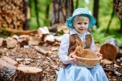 Blondes Mädchen im Hut, der ein Kaninchen hält Lizenzfreies Stockfoto