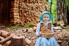 Blondes Mädchen im Hut, der ein Kaninchen hält Stockfoto