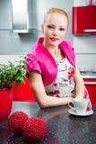 Blondes Mädchen im Innenraum der roten modernen Küche Stockfotos
