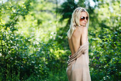 Blondes Mädchen im Kleid mit nackter Rückseite am Wald Stockfoto