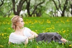 Blondes Mädchen im Löwenzahn Lizenzfreies Stockfoto