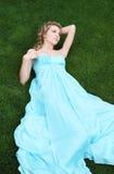 Blondes Mädchen im langen Kleid im Garten Lizenzfreies Stockbild
