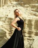 Blondes Mädchen im langen schwarzen Kleid, das im Sand aufwirft lizenzfreie stockbilder