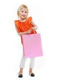 Blondes Mädchen im orange Hemd mit Einkaufstasche auf weißem Hintergrund Lizenzfreie Stockfotos