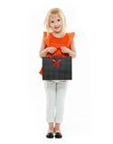 Blondes Mädchen im orange Hemd mit Einkaufstasche auf weißem Hintergrund Lizenzfreies Stockfoto