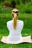 Blondes Mädchen im Park, der Yoga tut Lizenzfreie Stockfotografie