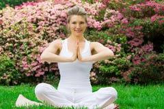 Blondes Mädchen im Park, der Yoga tut Stockbild