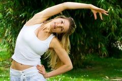 Blondes Mädchen im Park, der Yoga tut Lizenzfreies Stockfoto