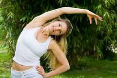 Blondes Mädchen im Park, der Yoga tut Stockfotos