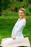 Blondes Mädchen im Park, der Yoga tut Lizenzfreie Stockfotos