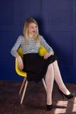 Blondes Mädchen im Rock und in der Weste sitzt auf einem Stuhl Stockbild