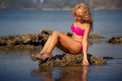 Blondes Mädchen im rosa Badeanzug sitzt auf Stein Stockfotografie