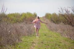 Blondes Mädchen im rosa Kleid läuft entlang Straße Stockfotografie