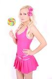 Blondes Mädchen im rosafarbenen Kleid mit Lutscher Stockfotos