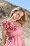 Blondes Mädchen im rosafarbenen Kleid mit Rosen Lizenzfreie Stockfotos