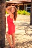 blondes Mädchen im Rot berührt Haarblicke in Kamera gegen Landhaus Stockfoto