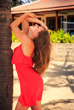 blondes Mädchen im Rot lehnt sich auf Palmenblicken aufwärts am Landhaus Stockbild