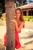 blondes Mädchen im Rot lehnt sich aus Palme heraus Lizenzfreie Stockfotografie