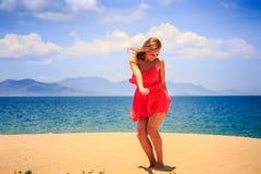 blondes Mädchen im Rot tanzt auf Sand Stockbilder