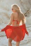Blondes Mädchen im roten Badeanzug auf dem Strand Stockbilder