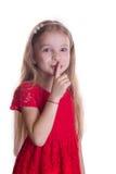 Blondes Mädchen im roten Kleid, das Finger bis zu den Lippen sagend shhh setzt Stockbilder