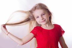 Blondes Mädchen im roten Kleid mit dem Wellenartig bewegen durch Windhaar Stockbild