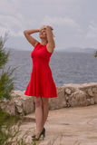 blondes Mädchen im roten Kleid steht nahe vom Meer Stockfoto
