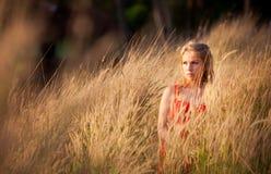 Blondes Mädchen im roten Kleiderstand im goldenen fild Lizenzfreie Stockfotografie