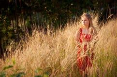 Blondes Mädchen im roten Kleiderstand im goldenen fild Lizenzfreie Stockfotos