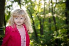 Blondes Mädchen im roten Mantel Lizenzfreie Stockfotos