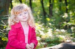 Blondes Mädchen im roten Mantel in grünem forrest Lizenzfreie Stockfotos
