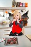 Blondes Mädchen im Schlägerkostüm Halloween-Kekse in der Küche essend Lizenzfreie Stockbilder