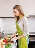 Blondes Mädchen im Schutzblech kochend mit Gemüse Lizenzfreie Stockfotografie