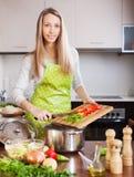 Blondes Mädchen im Schutzblech kochend mit Gemüse Stockfoto