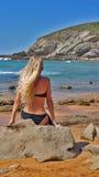 Blondes Mädchen im schwarzen Bikini, der zurück auf dem Stein sitzt Lizenzfreie Stockfotos