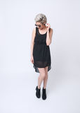 Blondes Mädchen im schwarzen Kleid auf weißem Hintergrund Stockfotos