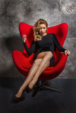 Blondes Mädchen im schwarzen Kleid, das auf dem roten Lehnsessel sitzt Stockbild