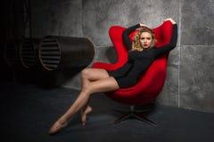 Blondes Mädchen im schwarzen Kleid, das auf dem roten Lehnsessel sitzt Lizenzfreies Stockbild