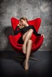 Blondes Mädchen im schwarzen Kleid, das auf dem roten Lehnsessel sitzt Stockfotografie