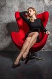 Blondes Mädchen im schwarzen Kleid, das auf dem roten Lehnsessel sitzt Lizenzfreies Stockfoto