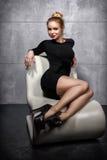 Blondes Mädchen im schwarzen Kleid, das auf dem weißen Lehnsessel sitzt Lizenzfreie Stockbilder