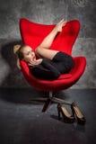 Blondes Mädchen im schwarzen Kleid liegt auf dem roten Lehnsessel Lizenzfreie Stockbilder
