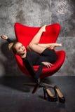 Blondes Mädchen im schwarzen Kleid liegt auf dem roten Lehnsessel Lizenzfreie Stockfotografie