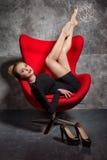 Blondes Mädchen im schwarzen Kleid liegt auf dem roten Lehnsessel Stockfoto