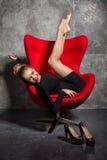 Blondes Mädchen im schwarzen Kleid liegt auf dem roten Lehnsessel Stockbilder