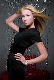 Blondes Mädchen im schwarzen Kleid und im breiten Gurt. Lizenzfreie Stockfotografie