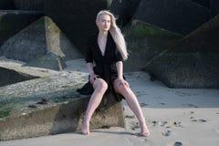 Blondes Mädchen im schwarzen Mantel auf Steinen Lizenzfreie Stockbilder